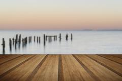 Beautiful calming long exposure landscape of ruined pier at sunset with woode - stock photo