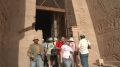 Abu Simbel temple, Egypt, exterior entrance with tourists, tilt up to statue Stock Footage
