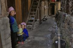 Two Chinese women and child, in courtyard of their house. - stock photo