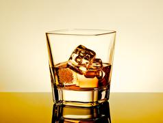 Whiskey in the glass on table with reflection, warm tint atmosphere Stock Photos