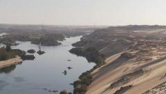 Aswan, Egypt, pan right to sand dunes across River Nile Stock Footage