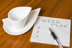 empty cup with handwriting week plan on napkin 2 - stock photo