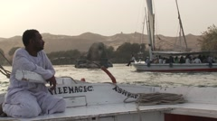 Felucca captain on Nile River at Aswan, Egypt at sunset, mid shot & closeup Stock Footage