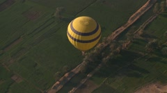 Hot air balloon over canal in Egypt's Nile Valley near Luxor, aerial view - stock footage