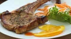 Battered fish steak and grilled pork chop steak. colourful salad and vegetable Stock Footage