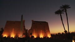 Karnak temple ancient Egyptian obelisk at dusk in Luxor, Egypt - tilt up to sky - stock footage