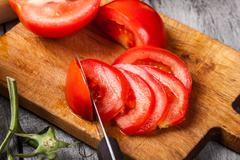 Chopped vegetables: tomatoes on cutting board. Selective focus Stock Photos