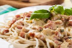 Spaghetti carbonara with bacon and basil on a plate Stock Photos