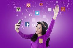Cheerful teenage girl holds cellphone with social media logo Stock Photos