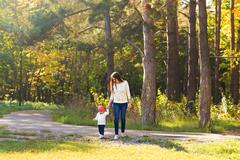 Young mother walking with her baby in an autumn park Stock Photos
