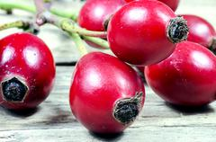 Detail of red rose hips on old wooden table - stock photo