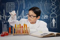 Little student playing chemical fluid Stock Photos