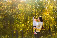 Young mother walking with her baby in an autumn park - stock photo