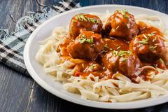 Pasta fettuccine and meatballs with tomato sauce on a plate Stock Photos