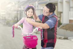 Man attaching helmet on the girl head - stock photo