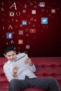 Stock Photo of Man using tablet on sofa with social network symbols