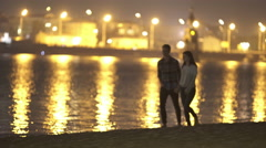 The couple (pair) walk on the embankment by river and city backround. Night time - stock footage