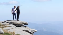 Couple in love on a top of rock mountain in Rila Lakes Park in Bulgaria Stock Footage