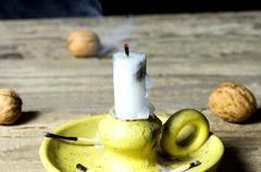 Not lit candle on wooden table with walnuts - stock photo