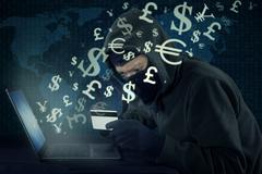 Thief stealing money with laptop and credit card - stock photo