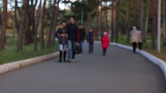 People walking in the park on a blurred image Stock Footage
