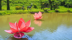 View of lake with artificial flowers in tropical tourist park Stock Footage