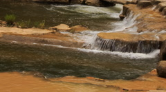 Closeup stream falls on plane surface among stones in park Stock Footage