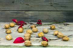Walnuts witk rose hips on an old wooden table - stock photo