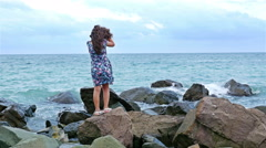 Little girl standing on the rocks on the sea shore and looking to the stormy sea Stock Footage