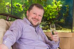Man sitting in armchair with glass of champaign - stock photo