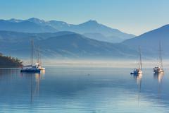 Anchored yachts at misty morning - stock photo