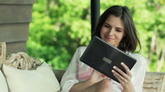 Young, pretty woman using tablet computer on sofa on terrace HD Stock Footage