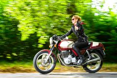 Active girl riding on the motorbike, slow motion, having fun in bikers tour Stock Photos