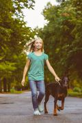 blonde girl walking with the dog or doberman in summer park. Warm toned photo - stock photo