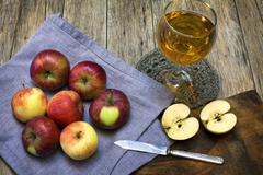 Still-life composition with red-ripe apples and juice in a glass. Stock Photos