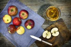 Still-life composition with red-ripe apples and juice on old wooden backgroun - stock photo