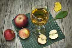 Beautiful composition with juice in a glass, apples and fallen leaves. - stock photo