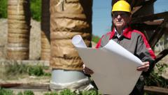 Worker in yellow hard hat with design drawings at heat station Stock Footage