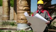 Stock Video Footage of Worker in yellow hard hat with design drawings at heat station