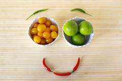 Healthy eating smiling face from vegetables and fruits on bamboo background. Stock Photos