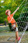Cute child, boy, climbing in a rope playground structure - stock photo