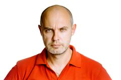 Unshaven fearsome middle-aged man in a red T-shirt. Studio. isolated - stock photo
