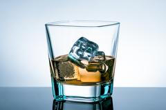 Glass of whiskey with ice cubes on bar table with reflection on light blue ti Stock Photos