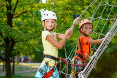 Cute children. Boy and girl climbing in a rope playground structure at adventure - stock photo