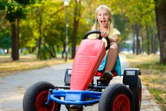 Beautiful happy little girl riding toy car in summer city park - stock photo
