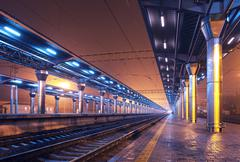 Stock Photo of Railway station at night. Train platform in fog. Railroad