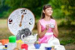 Girl sits at table and holding a cup of tea. Alice in Wonderland concept - stock photo