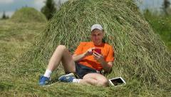 Man in orange t-shirt with smartphone and tablet PC sits near a haystack Stock Footage