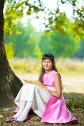 Beautiful teenage girl reads the book under huge oak tree on sunny summer day Stock Photos