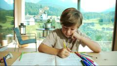 good kid doing homework at home in the mountains - stock footage